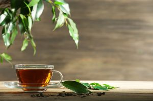 Cup of green tea on table on wooden background